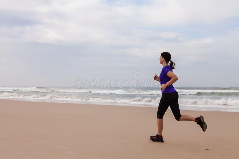 Funzionamento dell'atleta femminile alla spiaggia immagine stock libera da diritti