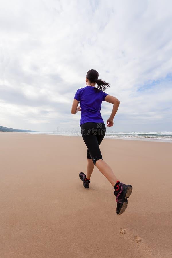 Funzionamento dell'atleta femminile alla spiaggia su un autunno fotografie stock