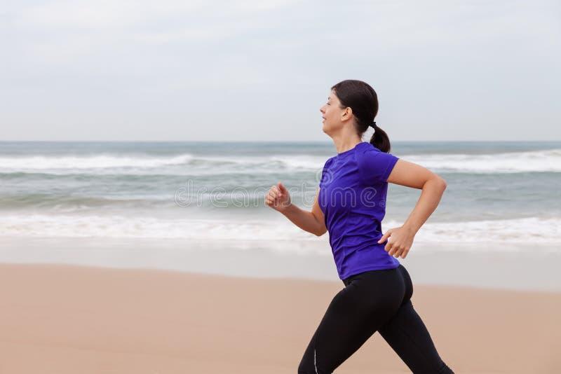 Funzionamento dell'atleta femminile alla spiaggia un giorno dell'autunno fotografia stock