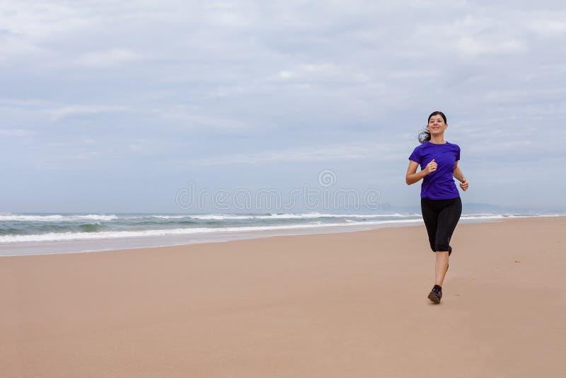 Funzionamento dell'atleta femminile alla spiaggia un giorno di autunno fotografia stock libera da diritti