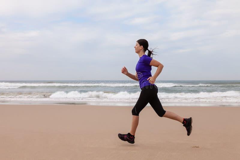 Funzionamento dell'atleta femminile alla spiaggia un giorno di autunno fotografie stock libere da diritti