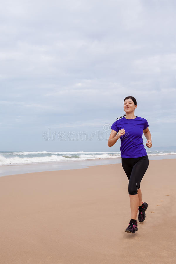 Funzionamento dell'atleta femminile alla spiaggia un giorno di autunno fotografia stock