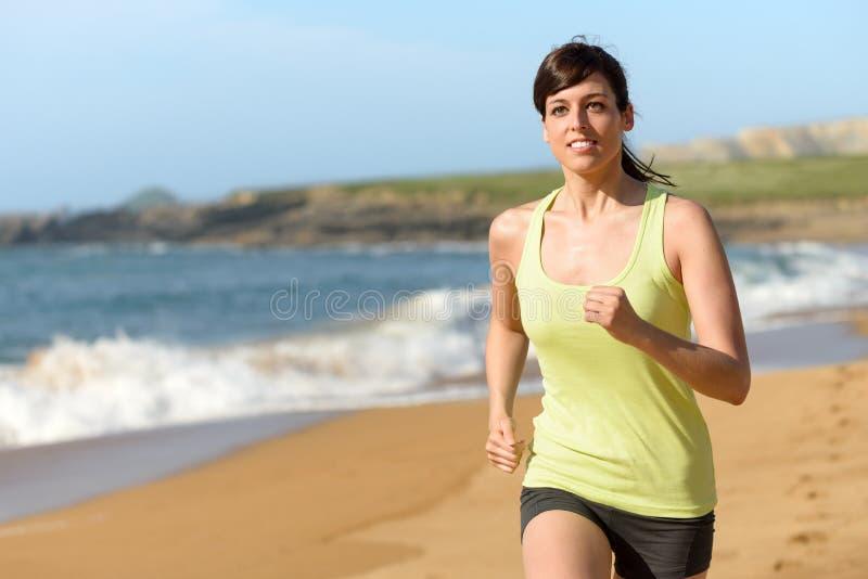 Funzionamento dell'atleta femminile sulla spiaggia fotografia stock