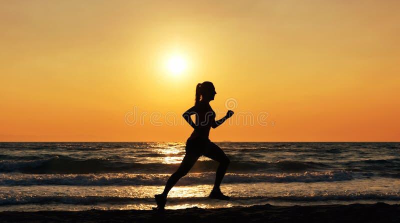 Funzionamento dell'atleta femminile sulla spiaggia al tramonto fotografia stock libera da diritti