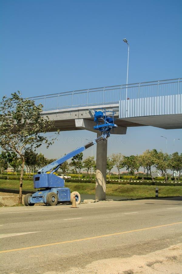 Funzionamento dell'elevatore sul cantiere un ponte immagine stock