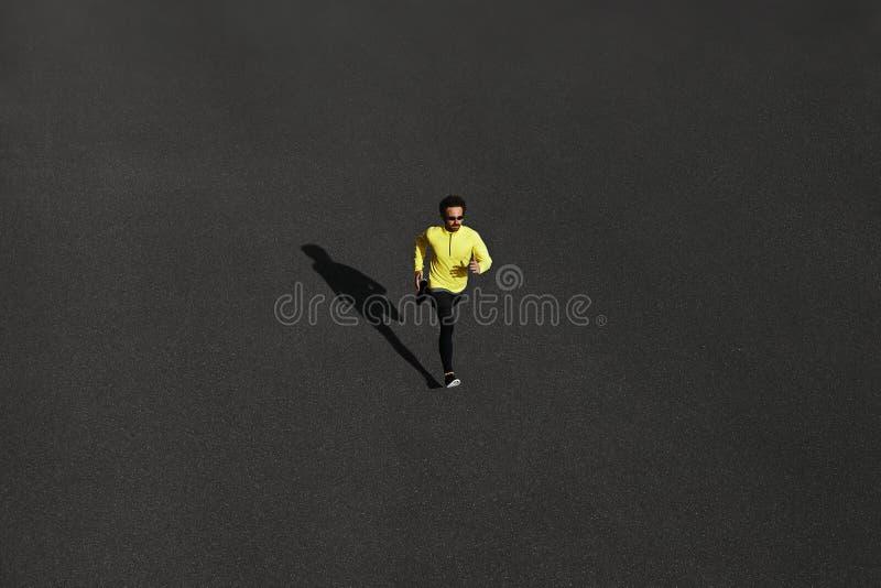 Funzionamento dell'uomo del corridore di vista superiore che sprinta per il successo sul funzionamento al blac fotografia stock