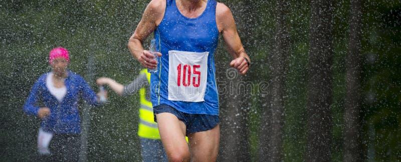 Funzionamento dell'uomo del corridore nell'ambito della maratona della città delle gocce di pioggia immagine stock