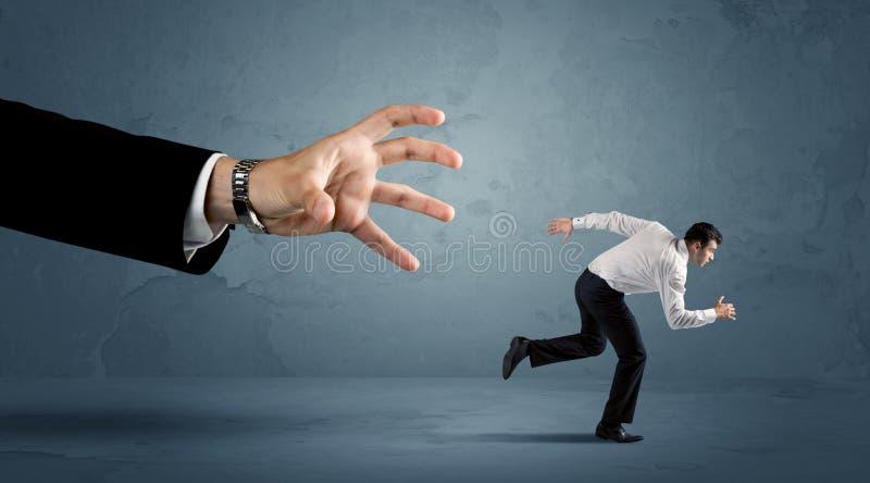 Funzionamento dell'uomo di affari a partire da un concetto enorme della mano fotografie stock