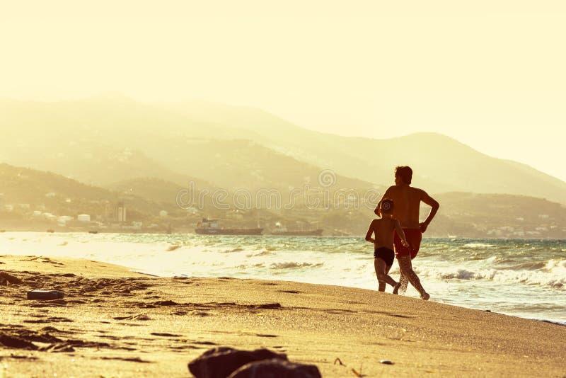Funzionamento dell'uomo e del ragazzo lungo la spiaggia contro il tramonto fotografia stock