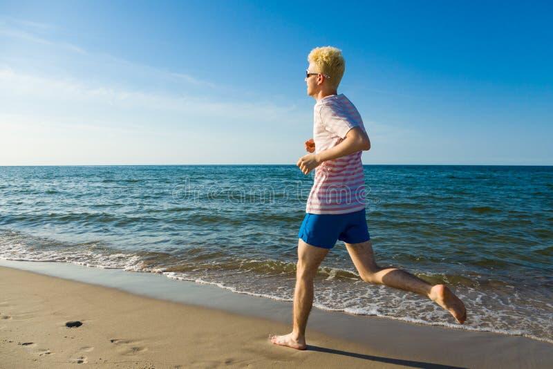 Funzionamento dell'uomo, saltante sulla spiaggia fotografie stock libere da diritti
