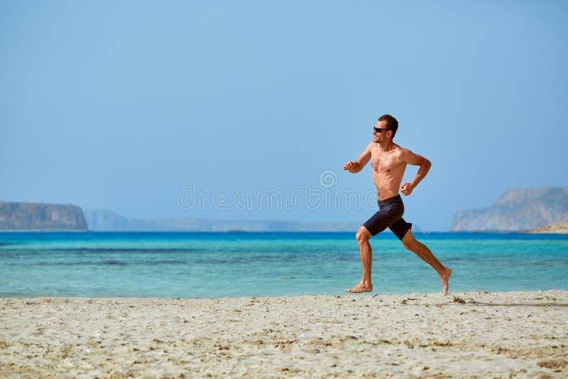 Funzionamento dell'uomo sulla spiaggia fotografia stock