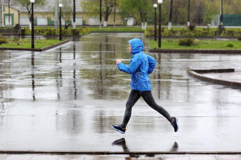 Funzionamento della donna del corridore nel parco nella pioggia Addestramento pareggiante per la m. immagine stock