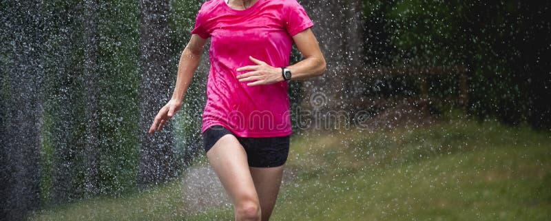 Funzionamento della donna del corridore nell'ambito della maratona della città delle gocce di pioggia fotografia stock