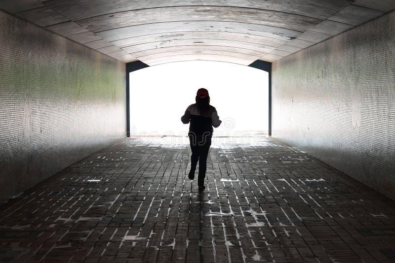 Funzionamento della donna dentro un tunnel fotografia stock