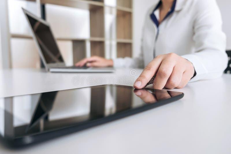 Funzionamento della donna di affari e computer portatile usando, compressa digitale fotografia stock
