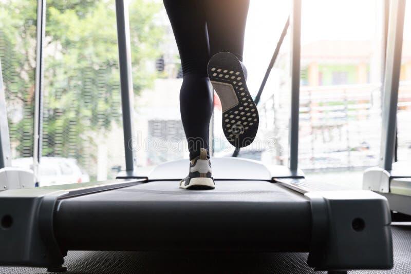 Funzionamento della donna di forma fisica sulla macchina di funzionamento alla palestra, cardio bruciante grasso immagini stock libere da diritti
