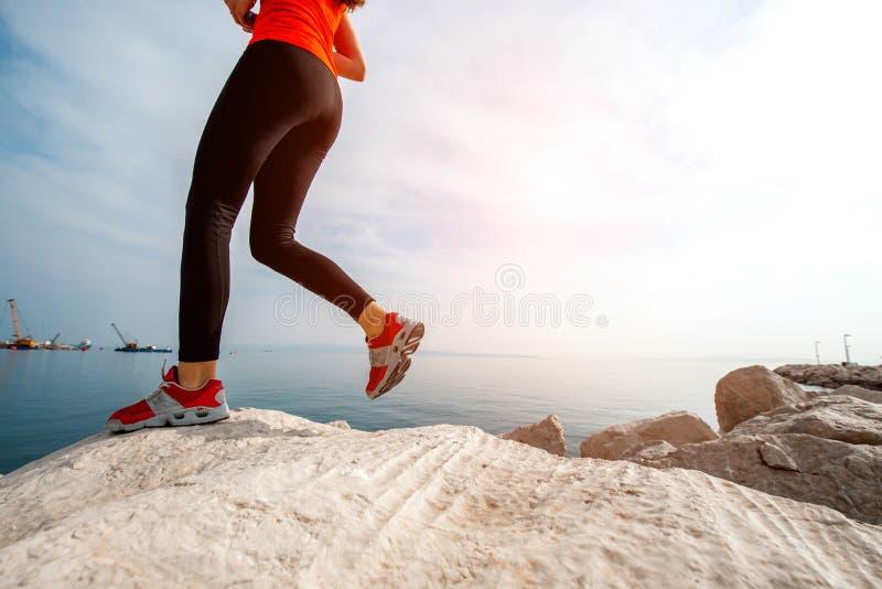 Funzionamento della donna di sport sulla spiaggia rocciosa immagine stock libera da diritti