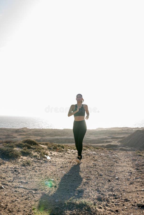 Funzionamento della donna lungo una strada sabbiosa marrone fotografia stock