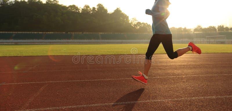 Funzionamento della donna nel corso della mattinata soleggiata sulla pista dello stadio fotografia stock