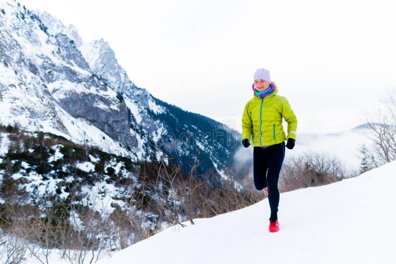 Funzionamento della donna nell'inverno, nell'ispirazione di forma fisica e nella motivazione fotografie stock libere da diritti