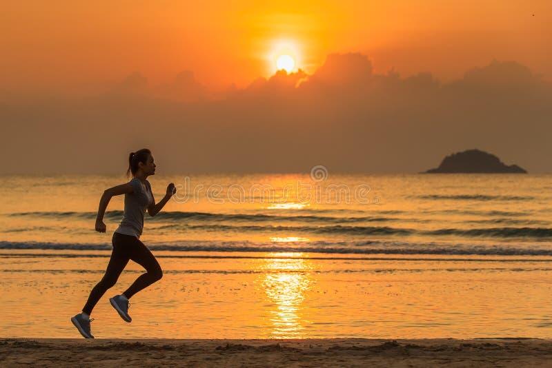 Funzionamento della donna sulla spiaggia ad alba fotografie stock