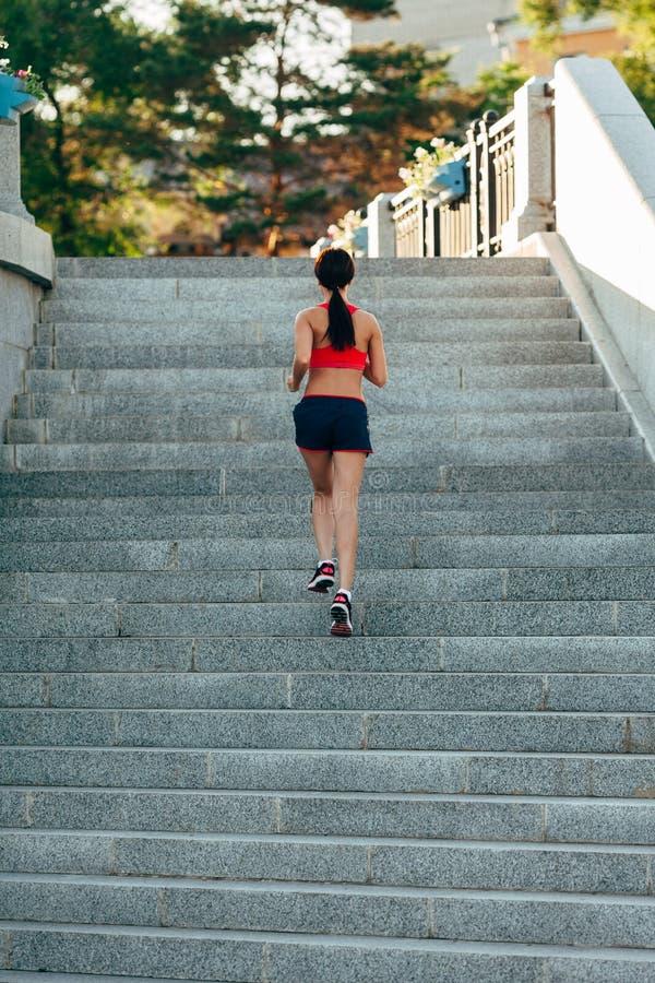 Funzionamento della donna sulle scale della città immagini stock