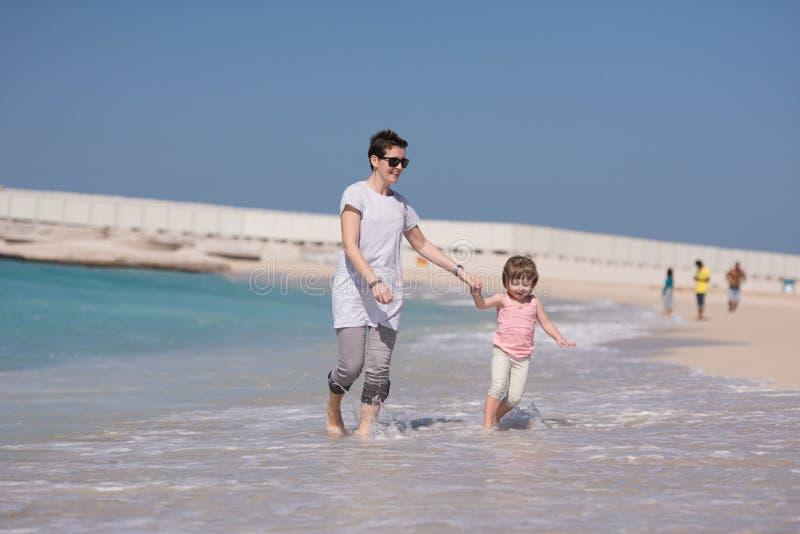 Funzionamento della figlia e della madre sulla spiaggia fotografie stock libere da diritti