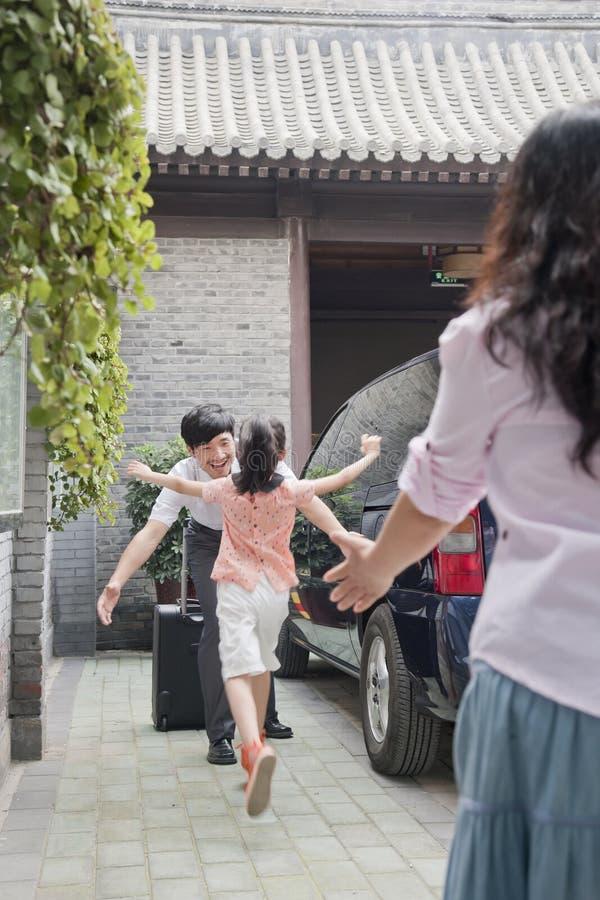 Funzionamento della figlia per abbracciare suo padre all'aperto dalla casa fotografia stock libera da diritti
