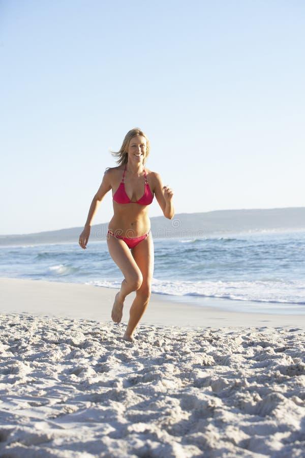Funzionamento della giovane donna lungo il bikini di Sandy Beach On Holiday Wearing fotografia stock