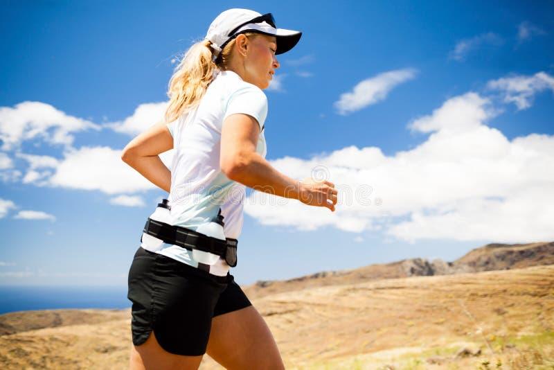 Funzionamento della giovane donna in montagne il giorno di estate soleggiato fotografia stock