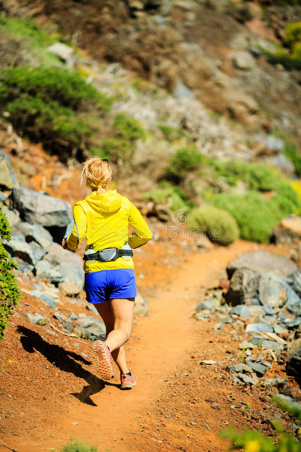 Funzionamento della giovane donna in montagne il giorno di estate soleggiato immagine stock