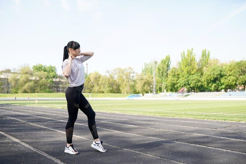 Funzionamento della giovane donna nel corso della mattinata soleggiata sulla pista dello stadio immagine stock libera da diritti