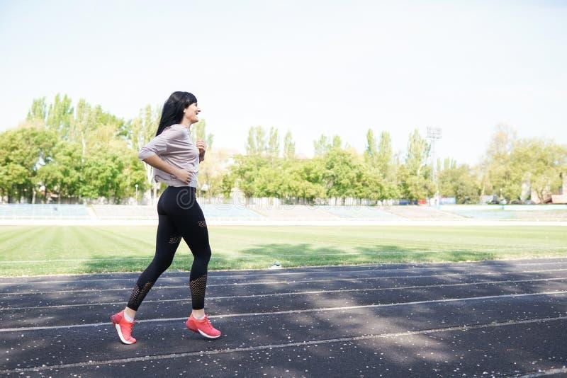 Funzionamento della giovane donna nel corso della mattinata soleggiata sulla pista dello stadio Perdita di peso Stile di vita san immagine stock libera da diritti