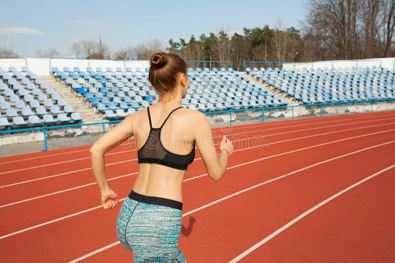 Funzionamento della giovane donna nel corso della mattinata soleggiata sulla pista dello stadio fotografie stock