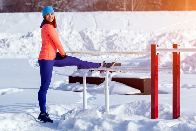 Funzionamento della giovane donna nell'inverno fotografia stock