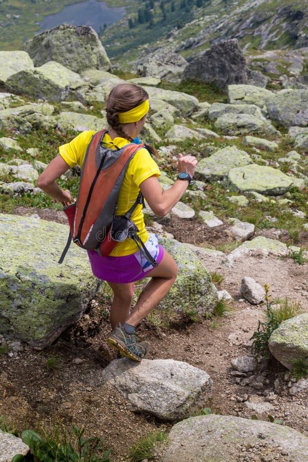 Funzionamento della giovane donna su un percorso asciutto della montagna immagine stock libera da diritti