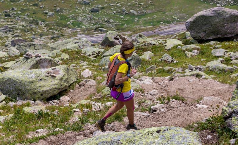 Funzionamento della giovane donna su un percorso asciutto della montagna fotografia stock libera da diritti