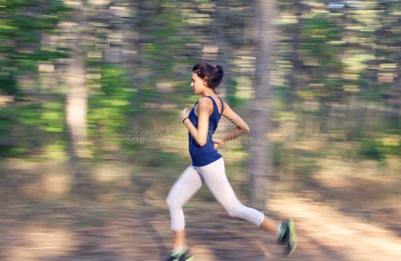 Funzionamento della giovane donna su una strada rurale nella foresta di autunno immagini stock