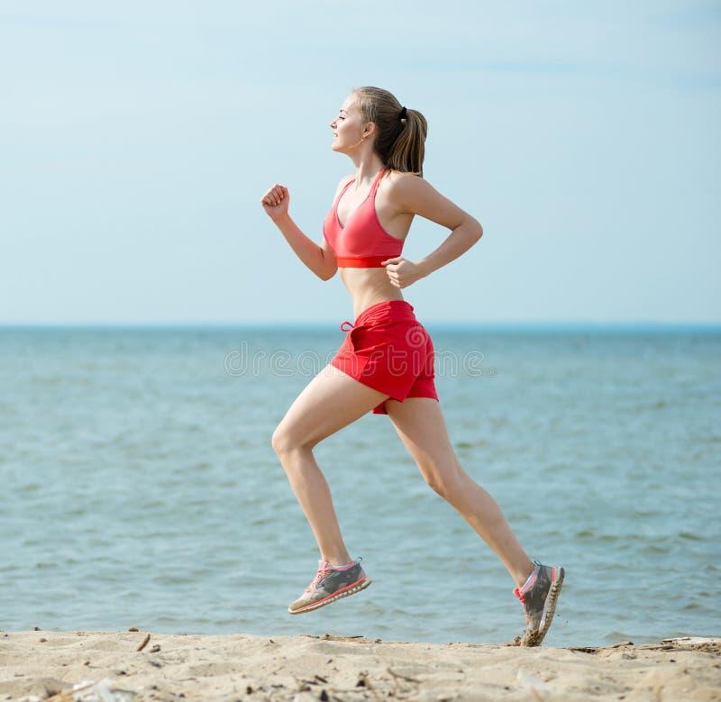 Funzionamento della giovane signora alla spiaggia di sabbia soleggiata di estate fotografie stock libere da diritti