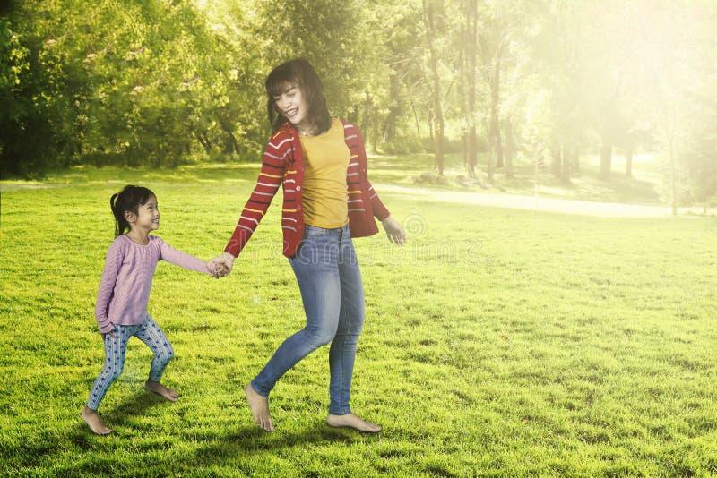 Funzionamento della madre e della ragazza al parco fotografia stock libera da diritti