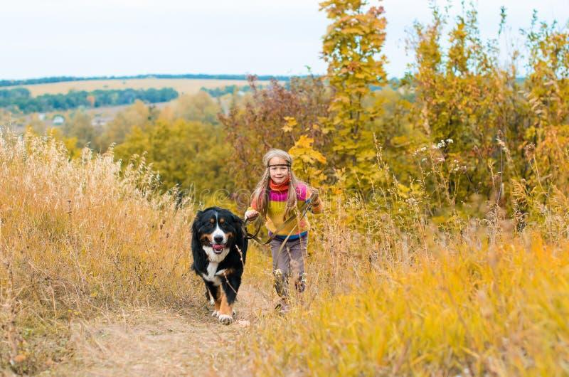 funzionamento della ragazza con il grande cane fotografia stock