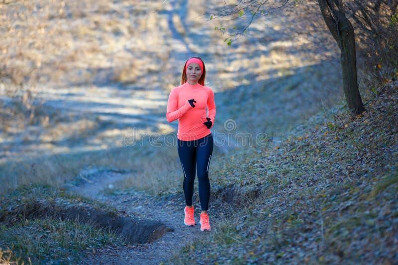 Funzionamento della ragazza nel parco nell'inverno in anticipo fotografia stock libera da diritti
