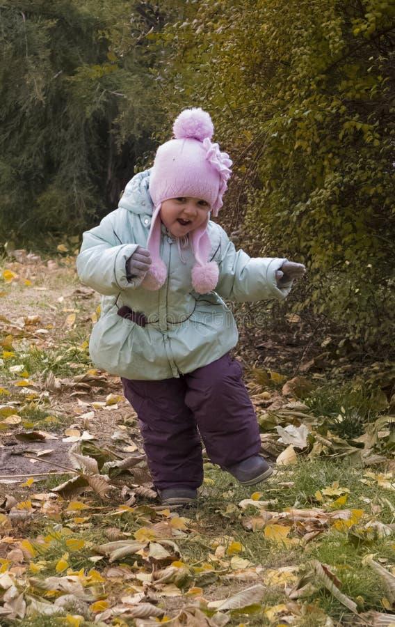 Funzionamento della ragazza sulle foglie gialle fotografie stock