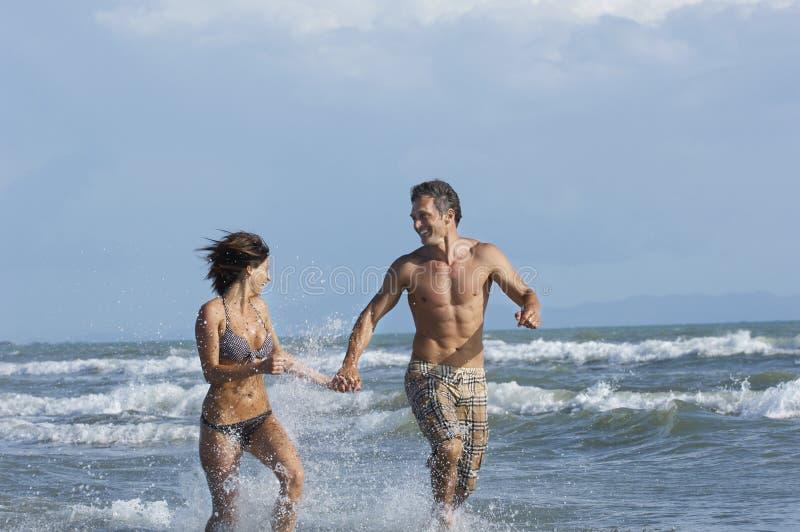 Funzionamento delle coppie in spuma alla spiaggia fotografie stock