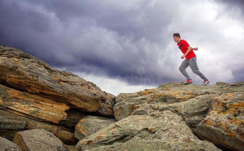 Funzionamento dello sportivo, saltante sopra le rocce nella zona di montagna fotografia stock