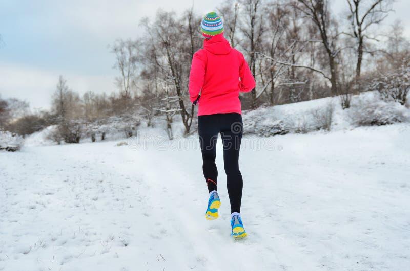 Funzionamento di inverno nel parco: vista posteriore del corridore della donna che pareggia nella neve, nello sport all'aperto e  immagine stock libera da diritti