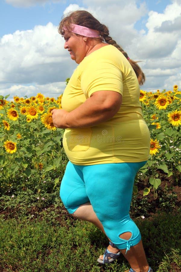 Funzionamento di peso eccessivo della donna lungo il campo dei girasoli immagini stock libere da diritti