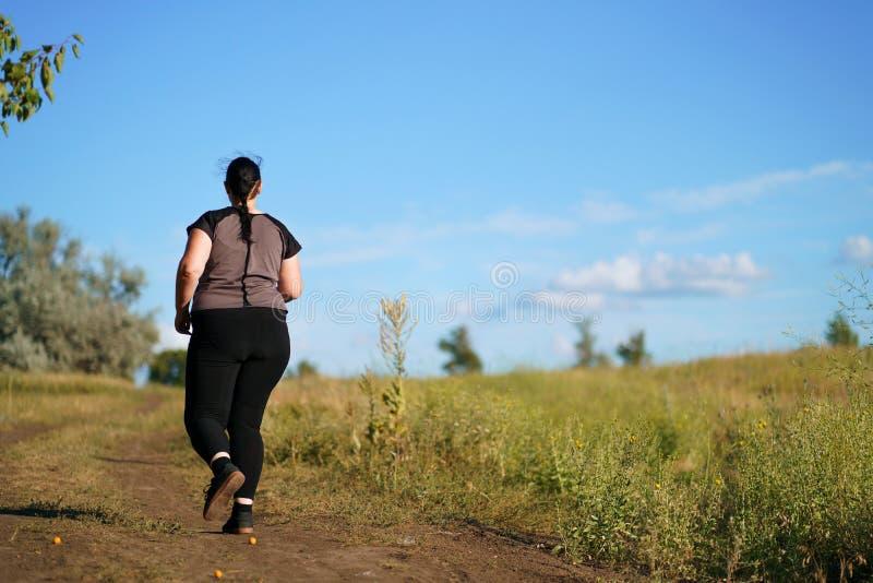 Funzionamento di peso eccessivo della donna sul prato di estate immagini stock libere da diritti