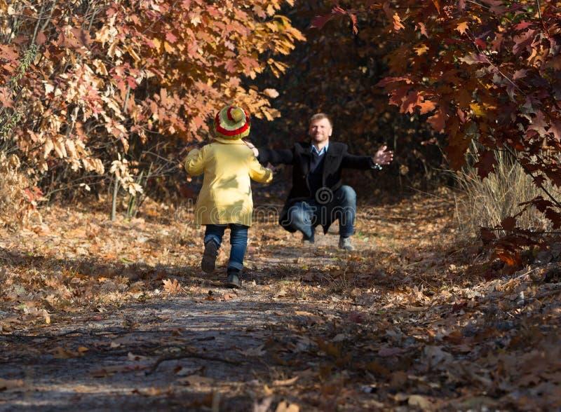 Funzionamento divertente della neonata verso suo padre su Forest Trail fotografia stock