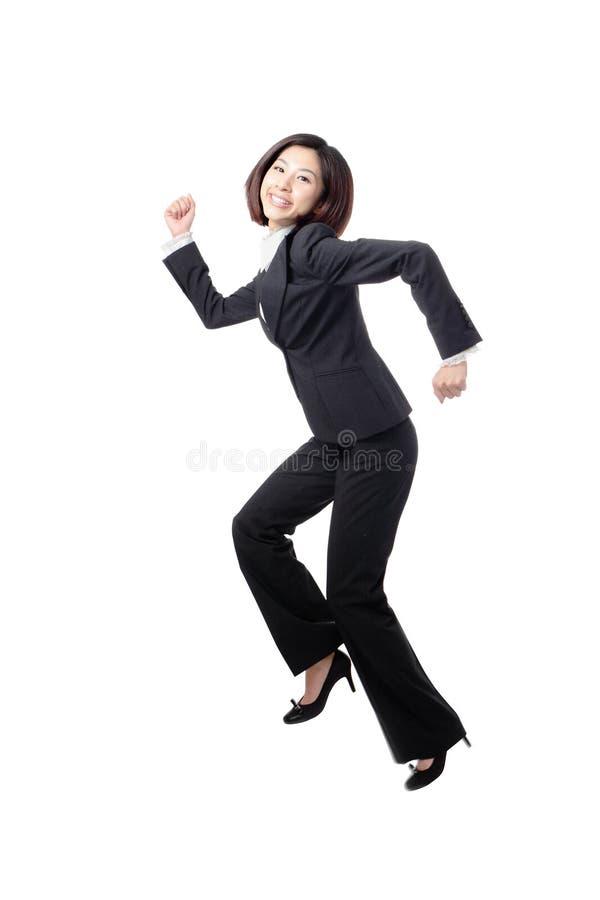 Funzionamento e salto felici graziosi della donna di affari fotografia stock